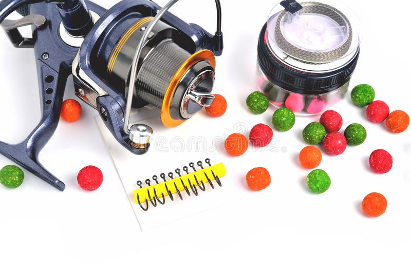 Fishing coil, carp hooks colored boilies, braided cord, on white background. Close-up stock photography