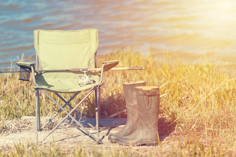 Fishing concept. Fishing chair on green grass with boots and spinning rod near lake. Toned stock photography