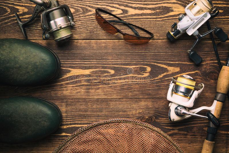 Fishing concept. Fishing rod and reels with rubber boots, polarized fishing glasses and cage on wooden background with free space royalty free stock photography