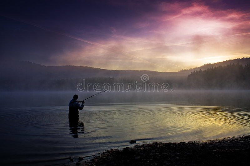 Fishing early in the morning. A male angler fishing in the river early in the morning royalty free stock image