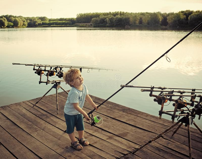Fishing equipment. Boy fisherman with fishing rods on wooden pier. Boy catch fish in river or lake water stock photography