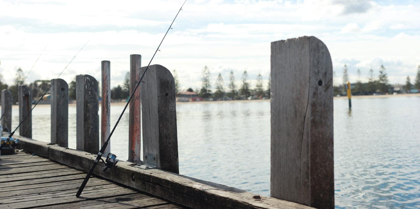 Fishing equipment cast into the ocean on an old timber jetty waiting for fish to bite. Coastal Victoria, Australia stock images