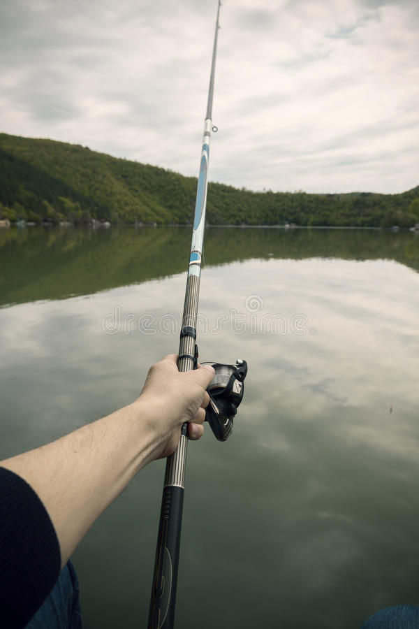 Fishing fish from shore with a stick stock photo