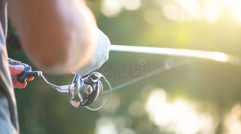 Fishing. Fisherman with a fishing rod on the river bank. Spinning. Fisher man catches a fish royalty free stock photos