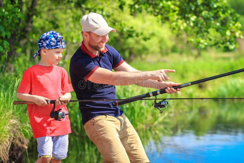Fishing. Fishermen on lakeside. Family fishing. Father and son on summer lake catch fish royalty free stock image