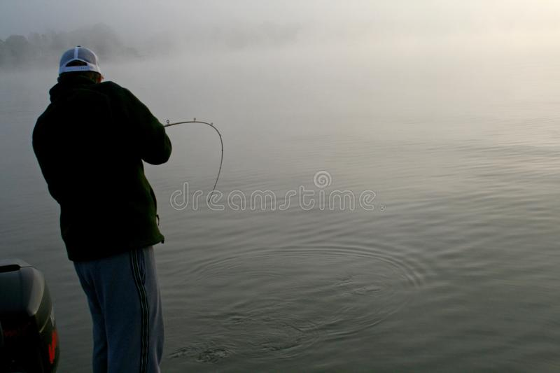 Fishing in the fog royalty free stock photography