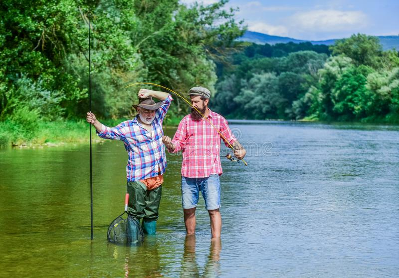 Fishing freshwater lake pond river. Mature man with friend fishing. Summer vacation. Happy cheerful people. Fisherman stock photos