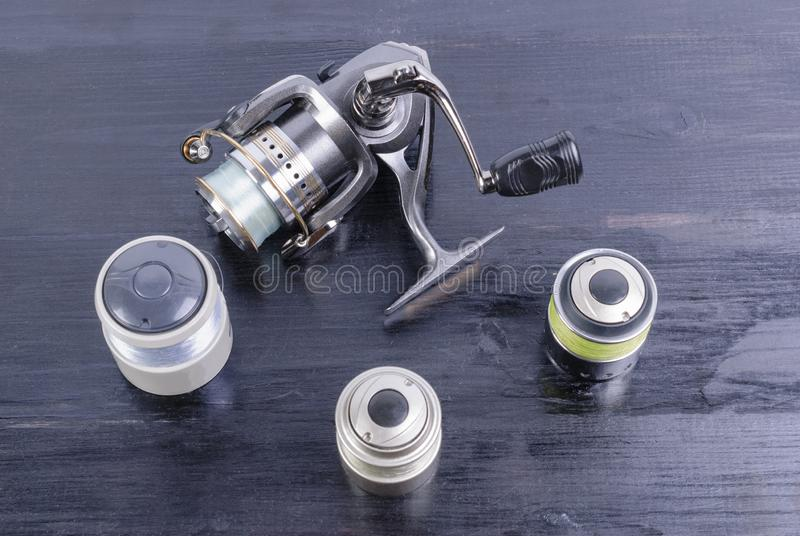 Fishing gear - spinning reel and fishing line on a wooden background. Silvery spinning reel, three spare spools with a fishing line on a dark wooden background stock photo