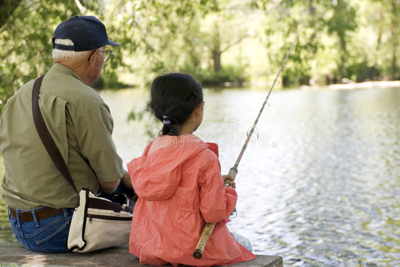 Fishing with Grandpa. A young girl is fishing with her grandpa on a warm summer day