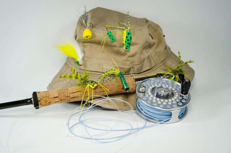 Fishing Hat with Fly Rod and Reel with Bass Flies. Close-up of a tan fishing hat with bass flies attached to it. Cork handle and fly rod and reel in the stock photos