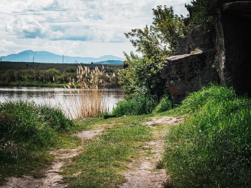 Dirt Road Next to Country Pond. A country dirt road ends at the shore of a pond and becomes a nice little spot to relax and fish, surrounded by grass and rocky royalty free stock images