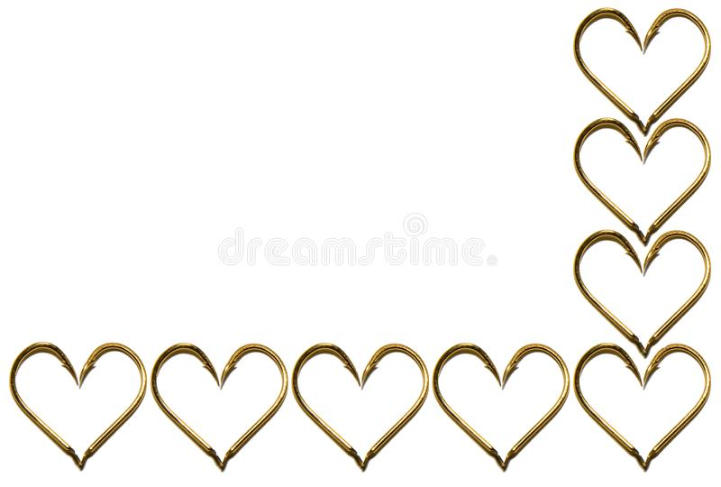 Fishing hooks in gold color. The hearts of the hooks. Abstraction. Isolated. Fishing hooks in gold color. The hearts of the hooks. Patterns of metal fishing royalty free stock photos