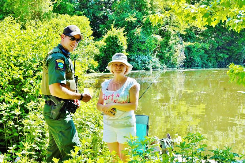 Fishing license check enviromental officer. Regulations on every lake of USA very specific ,even if you one time angler . The rod nearby you on the lake means stock photo