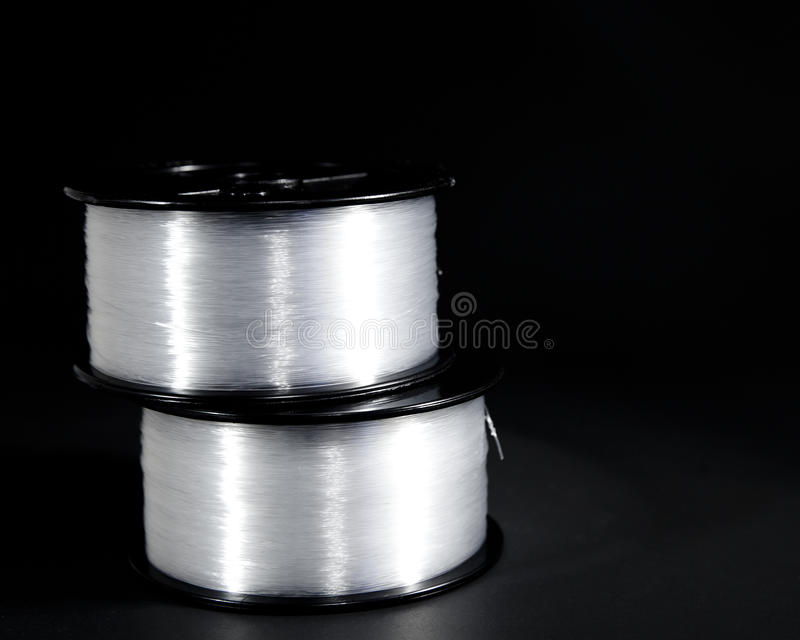 Fishing line. Two stacked spools of fishing line isolated on a black background stock photography