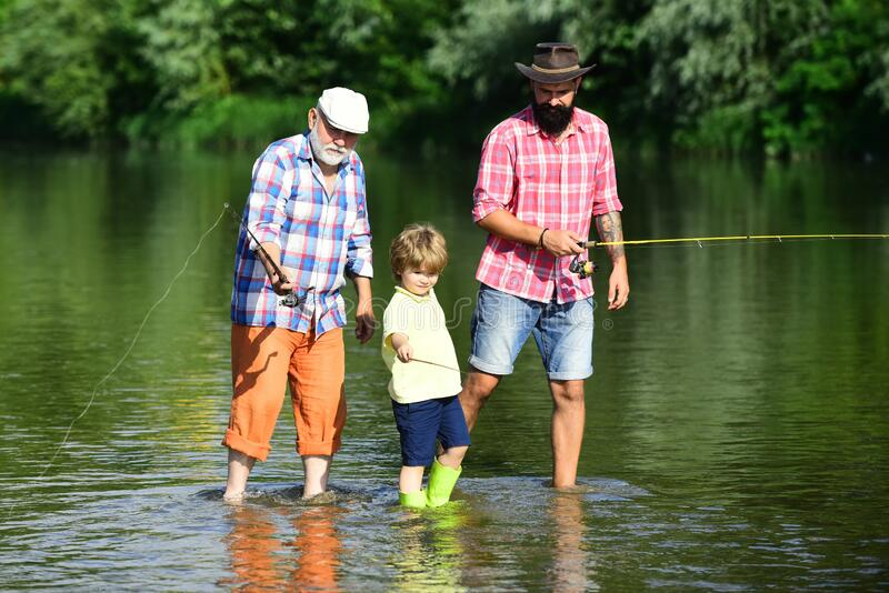 Fishing. Little boy fly fishing in river with his father and grandfather. royalty free stock photography
