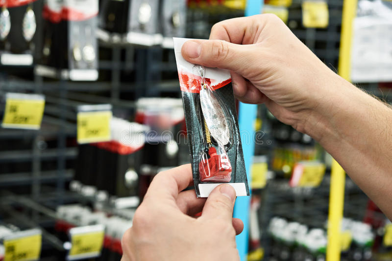 Fishing lure bait in hands man in store stock photography