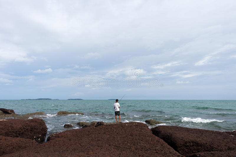 Fishing Man On Seashore. Rayong, Thailand - August 06, 2016: Unidentified Fishing Man On Seashore At Seascape Background stock photo