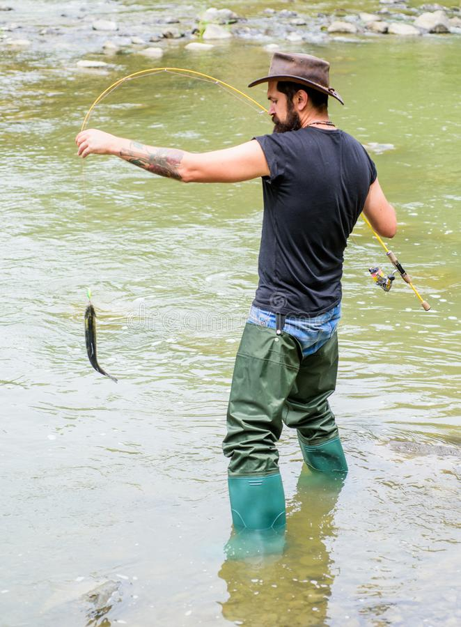 Fishing masculine hobby. Brutal man wear rubber boots stand in river water. Fisher weekend activity. Fisher with fishing royalty free stock image