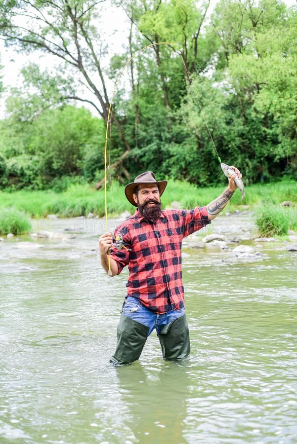 Fishing masculine hobby. Fisher fishing equipment. Fishing requires you to be mindful and fully present in moment. Fish. On hook. Brutal man wear rubber boots stock photo