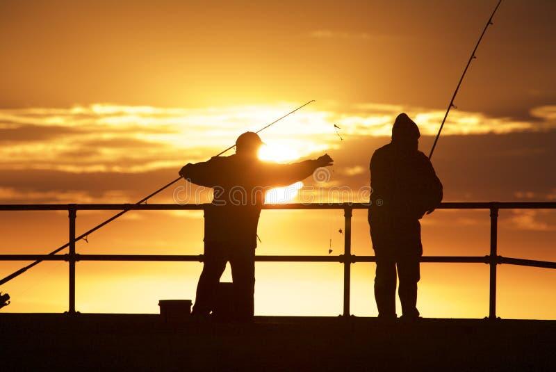 Fishing men at the beach royalty free stock photo