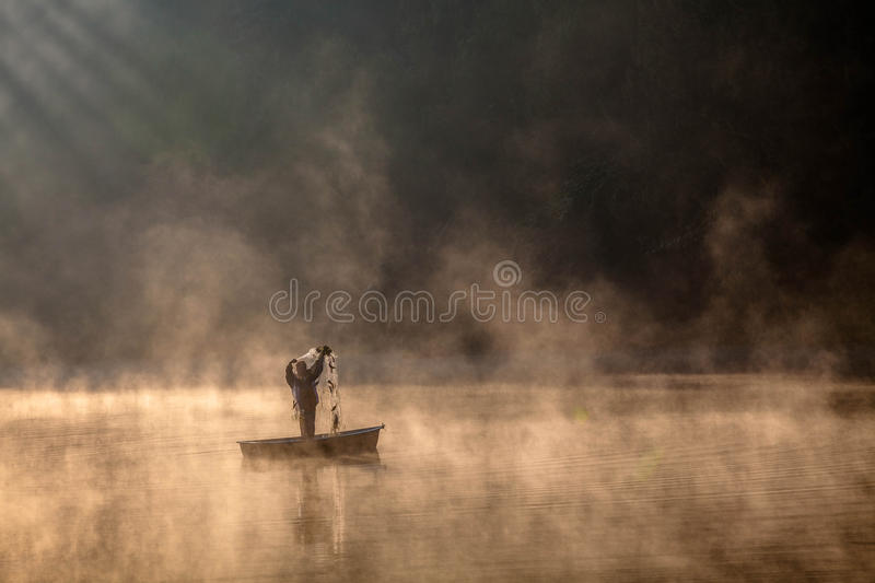 Fishing in the mist stock photography