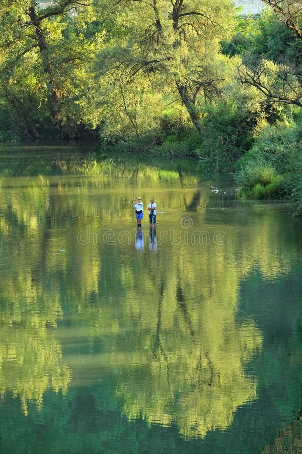 Fishing Morava River, Serbia. OVCAR BANJA, SERBIA - AUGUST 05, 2016: boy fishing under the watchful eye of his father in Morava River that flows in the lush royalty free stock photo