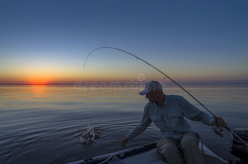 Fishing morning. Fisherman in boat catch fish.  royalty free stock photo