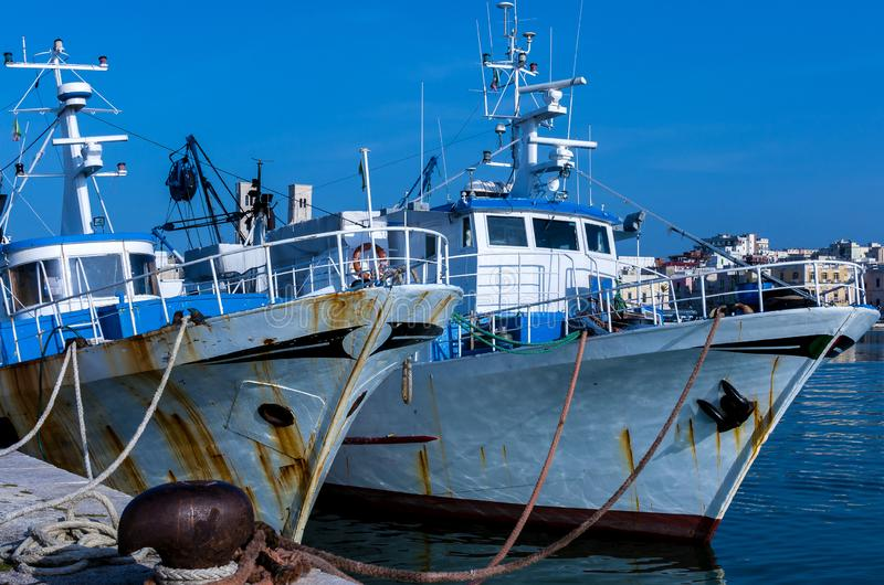 Fishing motorboats tied to mooring cleats. Of a port stock photography