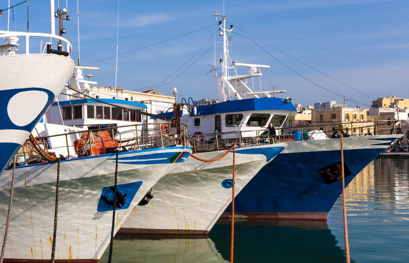 Fishing motorboats tied to mooring cleats. Of a port royalty free stock photos