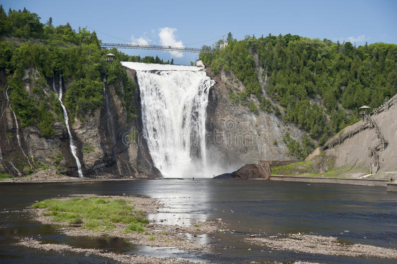 Fishing near Montmorency Falls. Fishermen in the river are dwarfed by the spectacular height of Montmorency Falls royalty free stock images