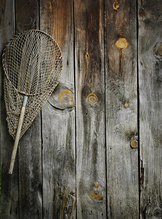 Fishing net. An old fishing net hanging on rustic wooden wall stock image