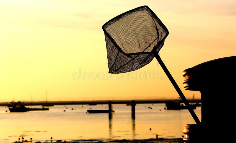 Fishing net in bin at sunset stock photography