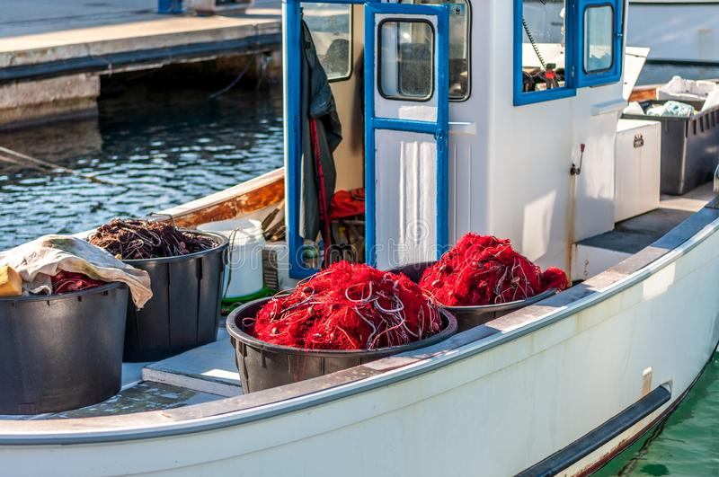 Fishing net on a boat. Fishing net on a small fishing boat, background, commercial, creek, pile, selective, sky, stow, striped, styles, summer, sun, tackle, tied royalty free stock image