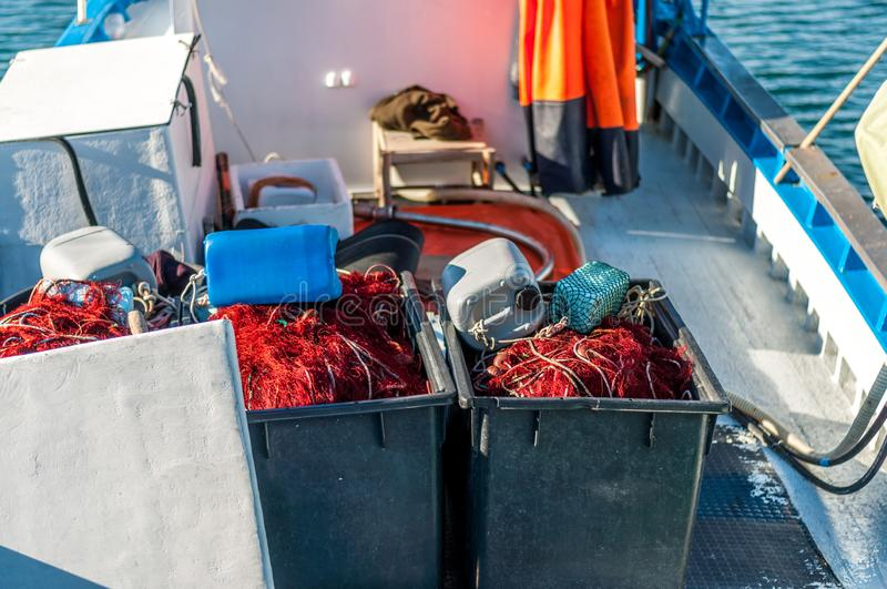 Fishing net on a boat. Fishing net on a small fishing boat, background, commercial, creek, pile, selective, sky, stow, striped, styles, summer, sun, tackle, tied stock image