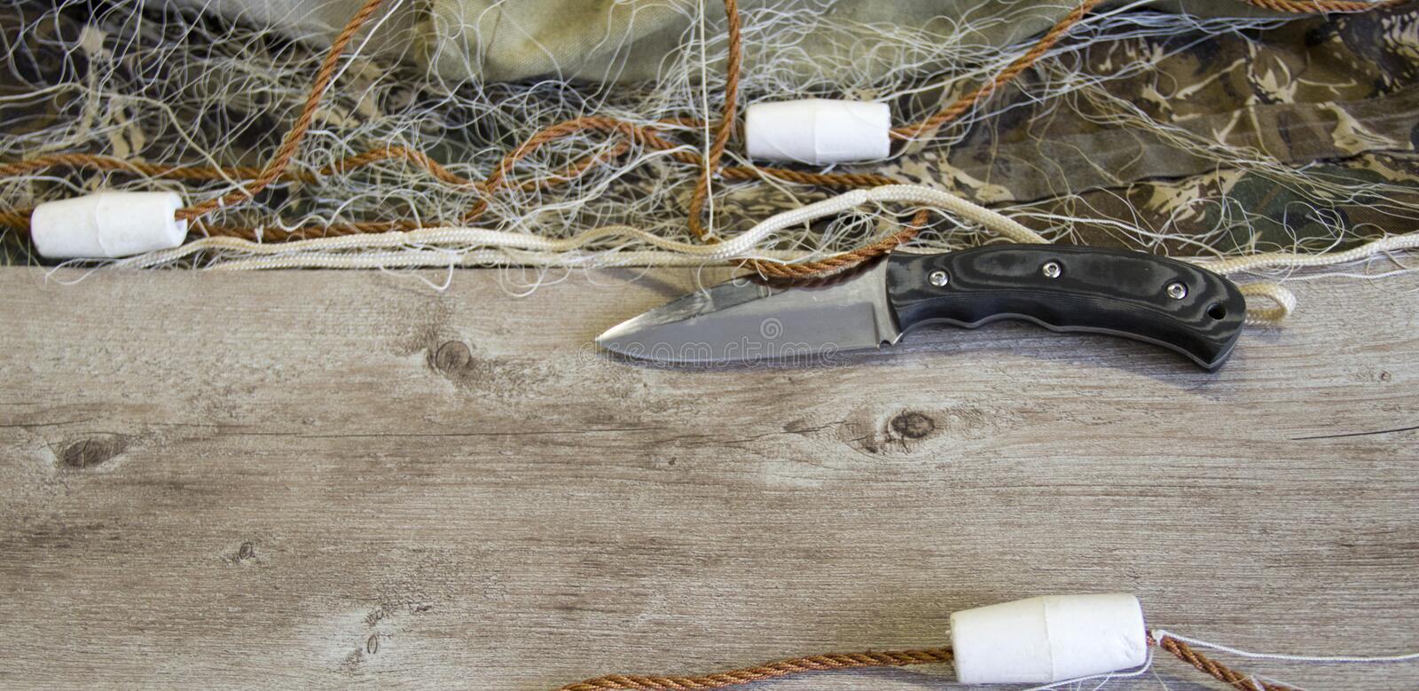 Fishing net with floats. And hunting knife stock image