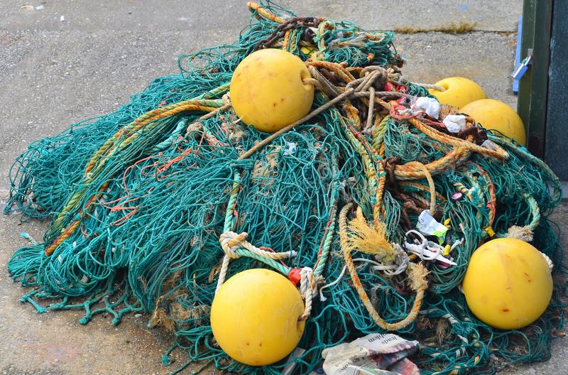 Fishing Net, New Zealand. Fishing net tangle on wharf at Akaroa harbour. Woven mess of netting and floats in a jumbled pile stock photography