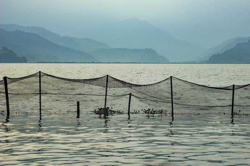 Fishing net over the lake water on the background of blurry mountains in the fog in the evening royalty free stock photography