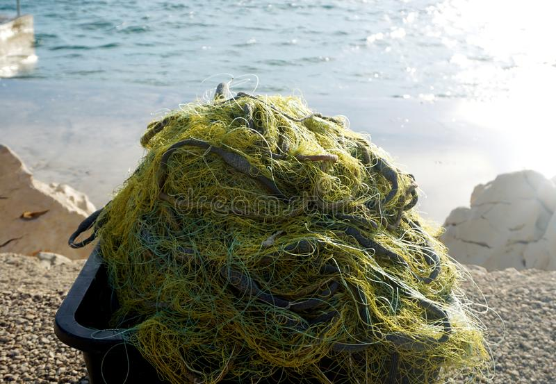 Fishing net in a square plastic bowl prepared for fishing. Fishing net in a square plastic bowl on the sea coast stock images