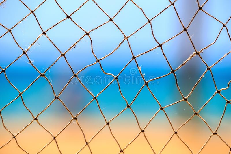 Fishing net at summer seaside on blue sky, sea and sandy beach abstract background.  stock image