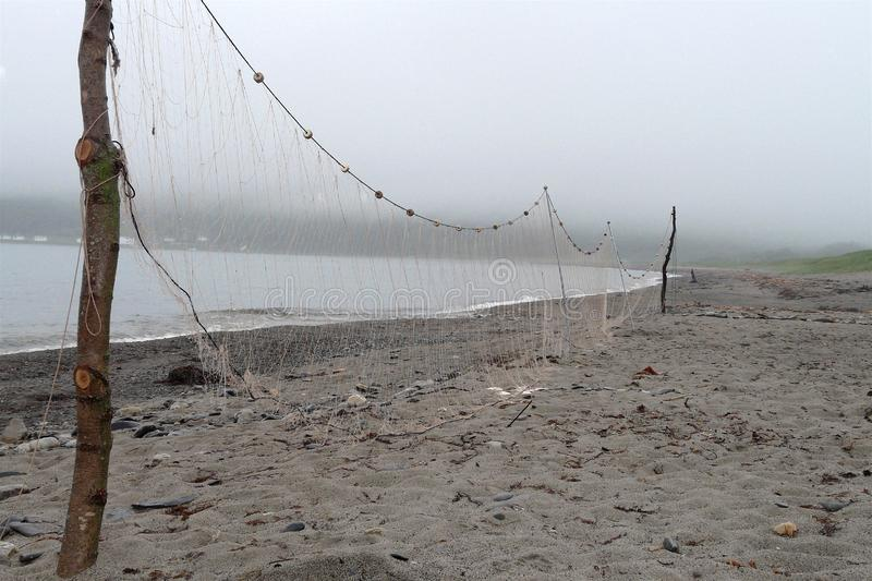 Fishing nets are drying on the beach in foggy weather stock photos