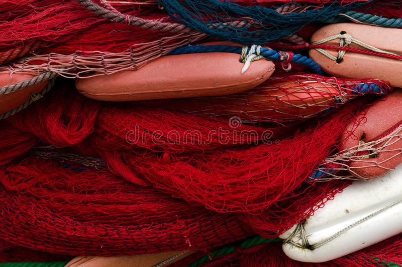 Fishing nets with floats. Background with blue and red netting royalty free stock images