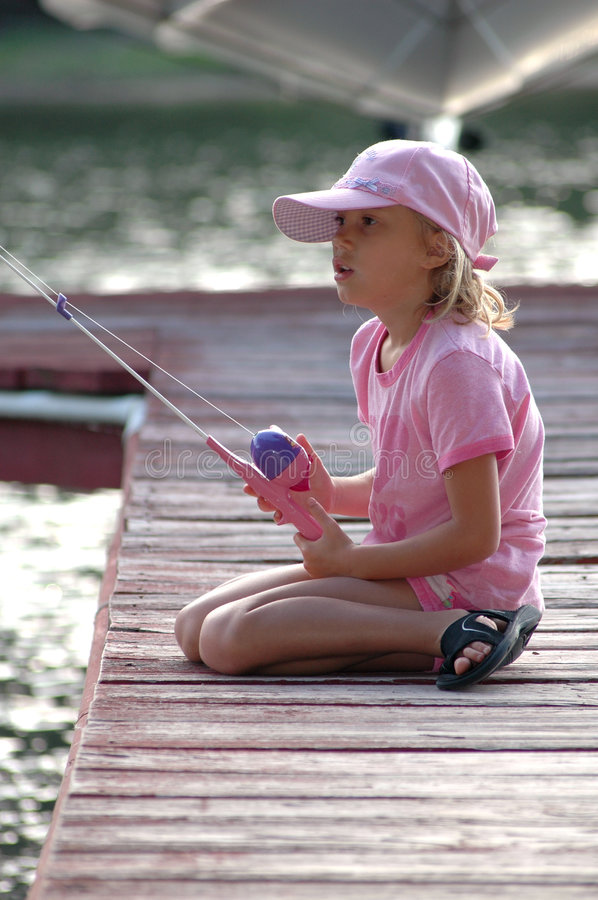 Fishing off dock. Little girl sits on the dock and fishes with her first fishing pole stock image