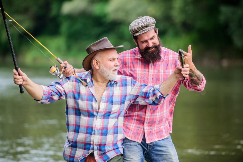 Fishing peaceful activity. Father and son fishing. Grandpa and mature man friends. Fisherman family. Rod tackle. Fishing royalty free stock photo