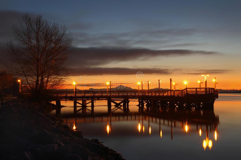 Fishing Pier Morning, Fraser River. A fishing pier on the bank of the Fraser River near Steveston at first light. Mount Baker, in the Cascade Mountain Range, in stock images