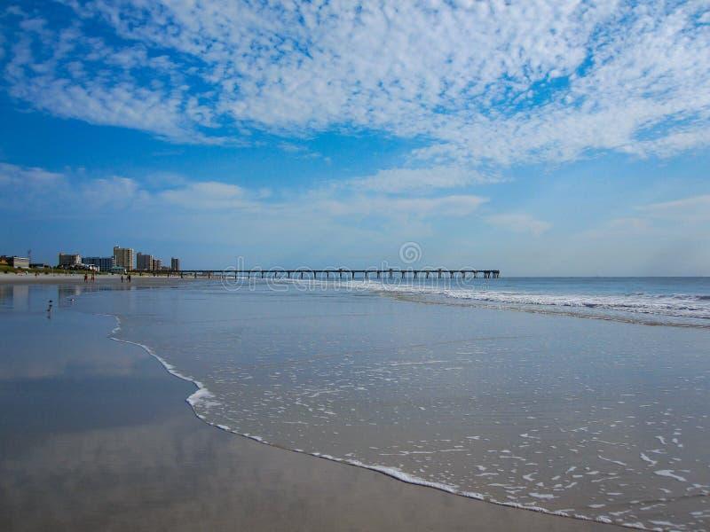 Fishing pier on beach on calm day stock photo