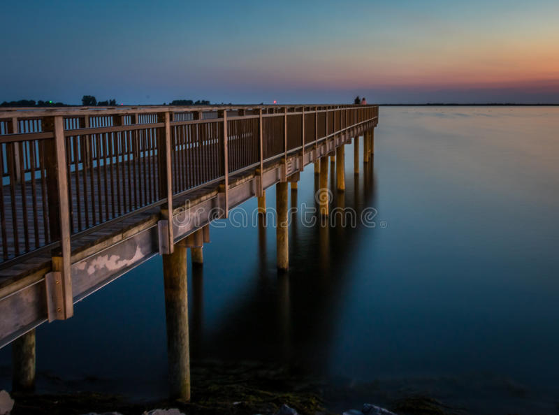 Fishing pier over Lake Erie at sunset. Wooden fishing pier over Lake Erie in New York at sunset royalty free stock images
