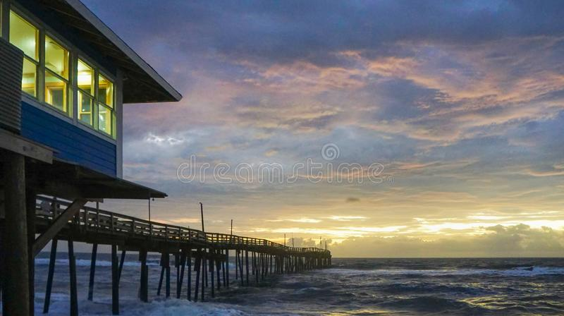 Fishing Pier at Sunrise Outer Banks NC. Fishing pier on the Atlantic Ocean at sunrise in Avon, North Carolina on the Outer Banks stock image