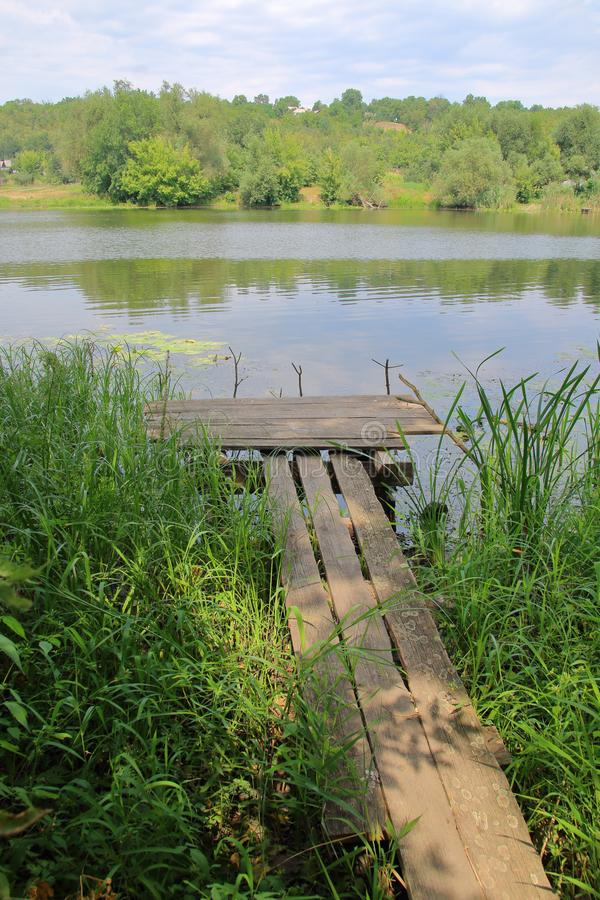 Fishing place. The picture was taken in Ukraine, on the South Bug River. In the photo there is a small bridge for fishing in the river. The bank of the river is royalty free stock images