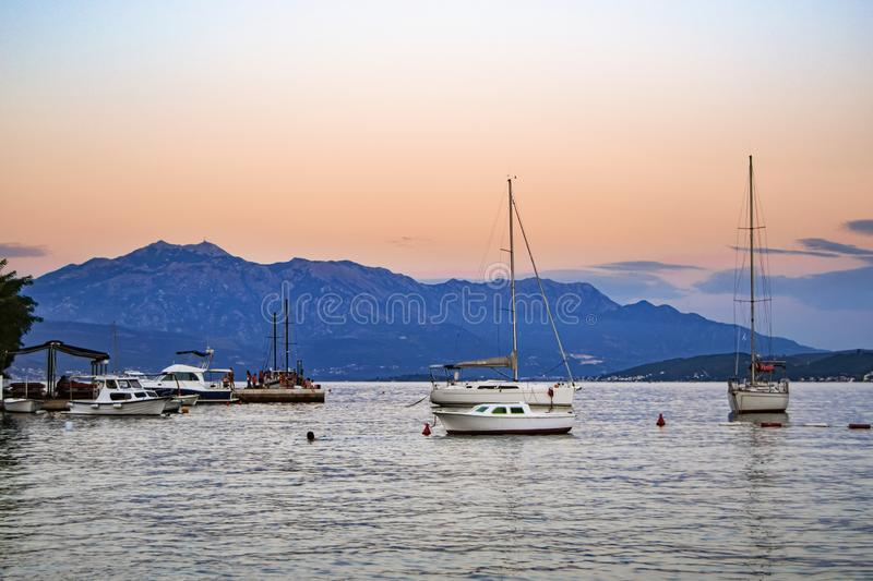 Fishing and pleasure boats at anchor in a picturesque sea bay at sunset stock image