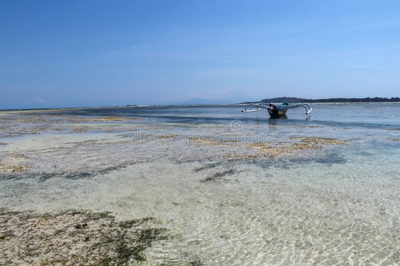 Fishing and pleasure boats on sand at low tide. Fishing boat at ebb tide in Gili Meno, Indonesia. Traditional wooden boat beached. stock images